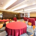 Round tables with red linen coverings surronded by chairs