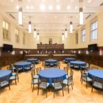 A large room with blue banquet tables and 8 chairs surronding each. There ar a total of 8 tables with 8 chairs each totaling 64 chairs.