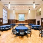 A large room with blue banquet tables and 8 chairs surronding each with a stage upfront