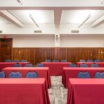 The Ben Franklin Meeting Room set in a classroom style setup, with rectangular tables dressed in burgundy linen set up with three chairs each all facing the same direction