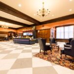 A shot of the main lobby of Houston Hall showing the center welcome desk and two small lounge areas with plush lounge furniture
