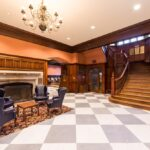 A Shot of the western side Main Lobby of Houston Hall, showing one of the ornate wooden staircases to the second floor and a working fireplace surrounded by cozy plush armchairs