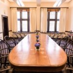 A wooden conference table with capitain chairs around it