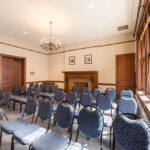 Brachfeld Meeting room set to accommodate 30 guests in a theatre set up, showing the faux fireplace and chandelier lighting