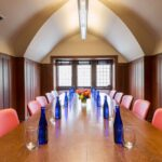 Closeup of the Morris Seitz Conference Room Table. A gourmet beverage is located at each seat with a floral centerpiece
