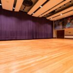 Interior of Emily Sachs Rehearsal Room showing the dance floor and mural with the mirrors closed by a large purple curtain
