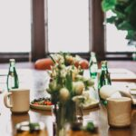 A closeup of the conference table with coffee cups and Perrier along with a tray of food and floral arrangement