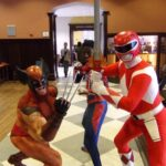A Power Ranger, Spiderman, and Wolverine pose for pictures near a bell